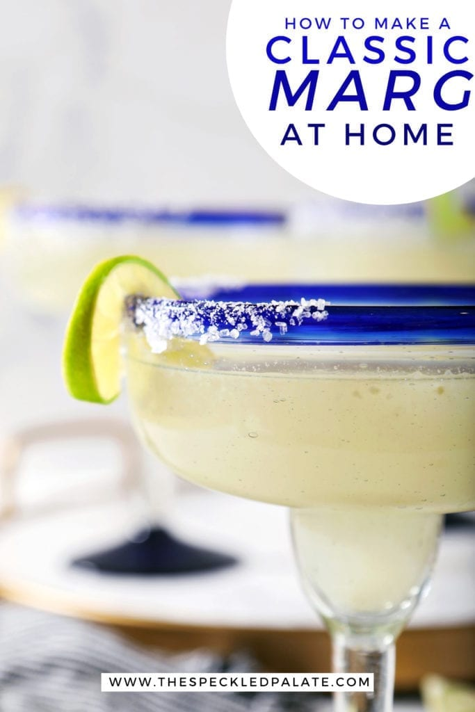 Close up of a lime twist on the salted rim of a margarita with the text 'how to make a classic marg at home'