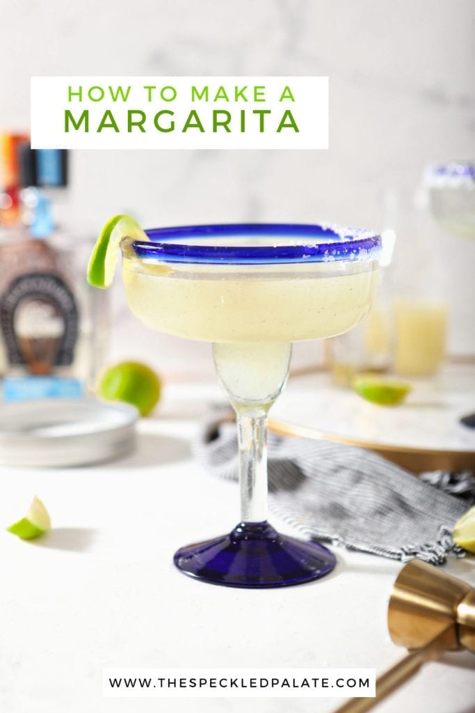 A margarita sits on a marble counter in front of ingredients with the text 'how to make a margarita'