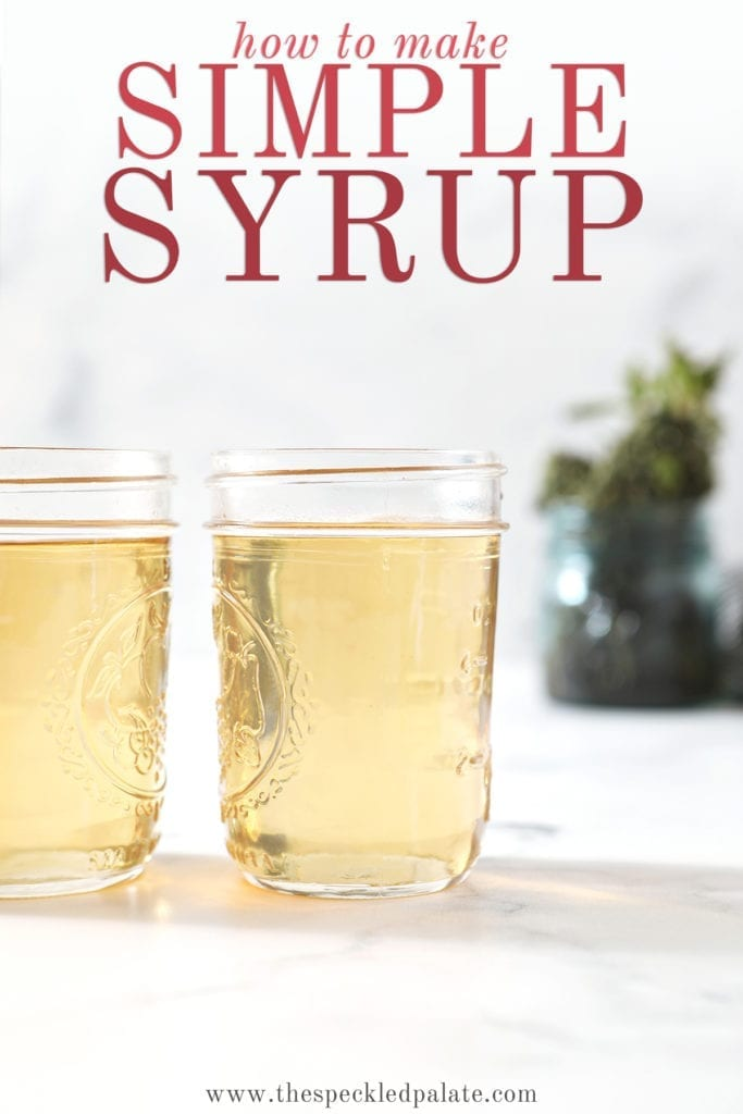 Two jars holding simple syrup sit on a marble surface in front of a jar holding fresh mint leaves with the text 'how to make simple syrup'