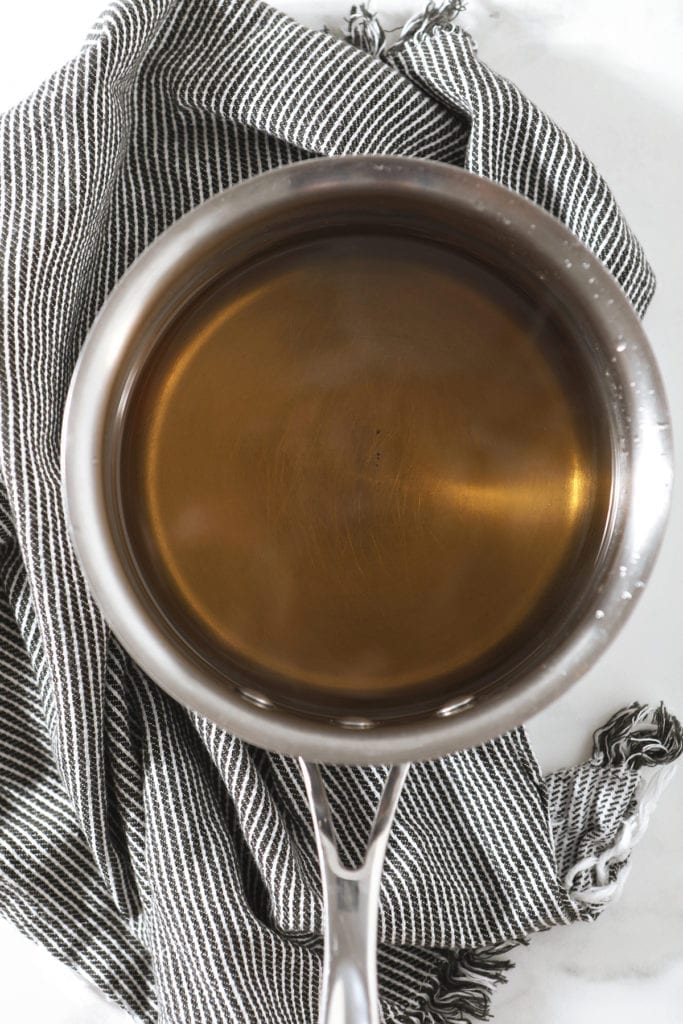 Simple syrup in a saucepan sits on top of a gray and white striped towel