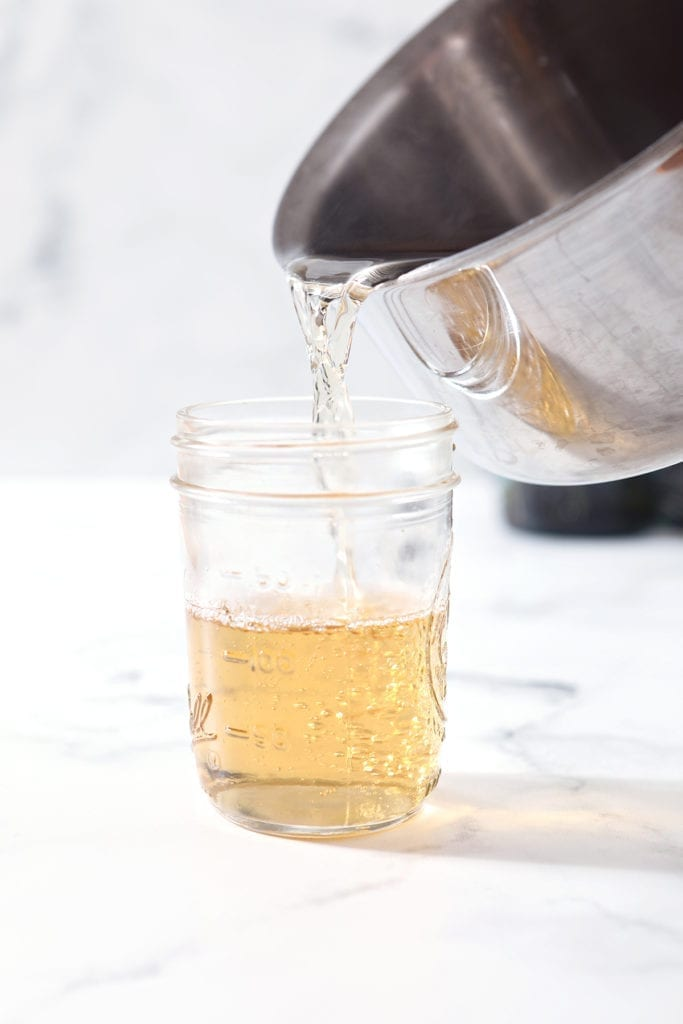 pouring simple syrup from a pot into a glass jar