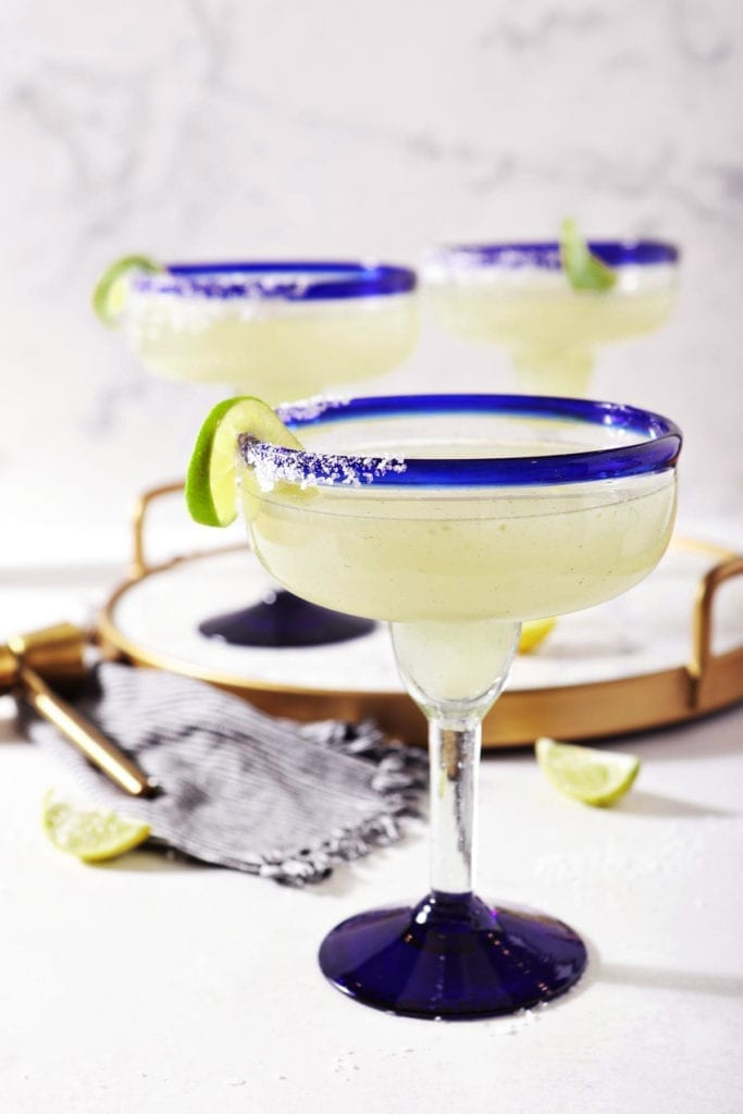 A salt-rimmed glass holding a classic margarita recipe sits on marble, in front of a marble tray holding two more