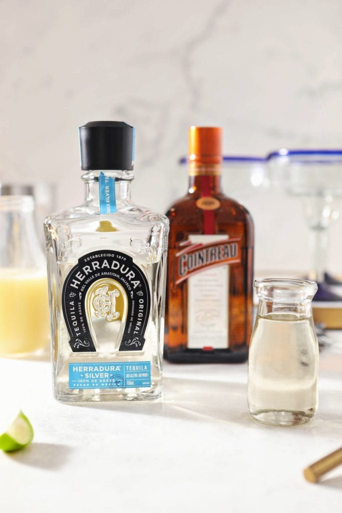 A bottle of tequila sits next to lime juice, simple syrup and a bottle of Countreau on a marble counter
