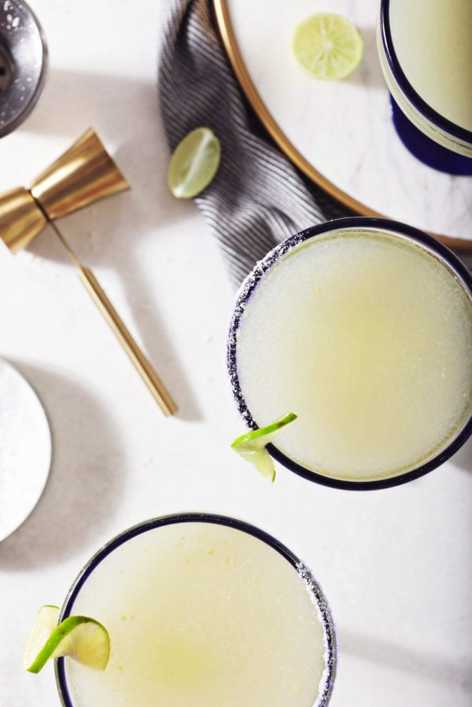Three Cointreau margaritas sit on a marble counter next to a jigger, lime wedges and a container of salt