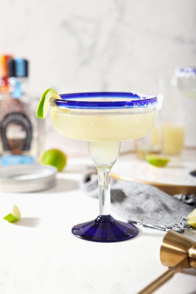 A margarita sits on a marble counter in front of ingredients