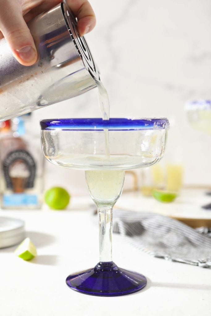 A person pours a drink into a salt-rimmed blue margarita glass