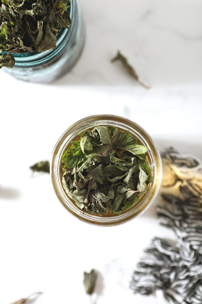 Mint leaves sit on top of a jar of simple syrup before being stirred in