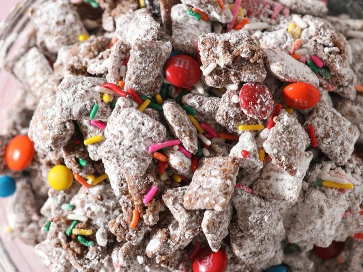 Close up of a bowl with rainbow sprinkles and chocolate-covered candies in Chex Mix Puppy Chow