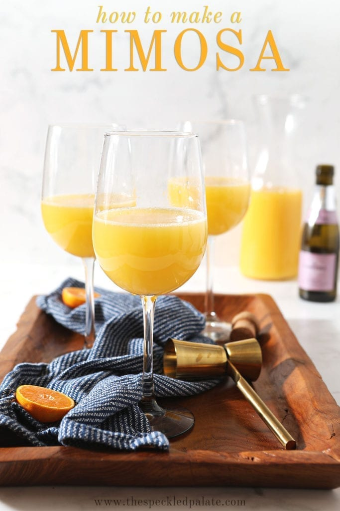 Three mimosas sit on a wooden tray with a dark blue towel with the text 'how to make a mimosa'