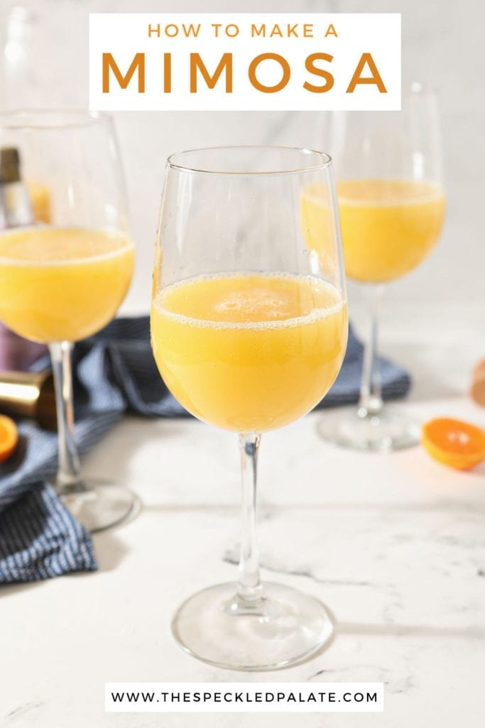 A prosecco mimosa in a wine glass sits in front of two more on a marble countertop