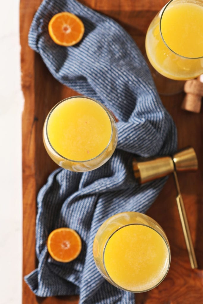 Three wine glasses holding orange juice and champagne sit on a wooden tray