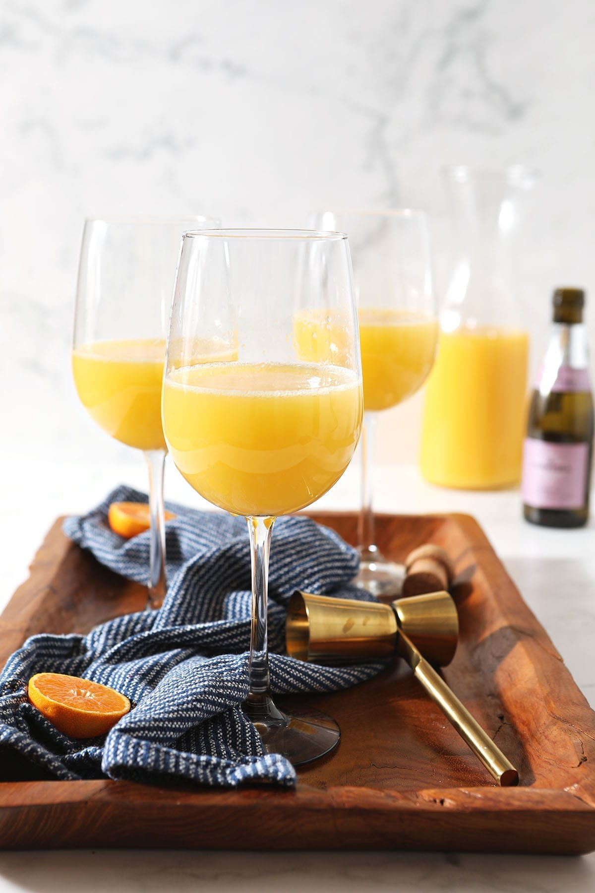 Three mimosas sit on a wooden tray with a dark blue towel