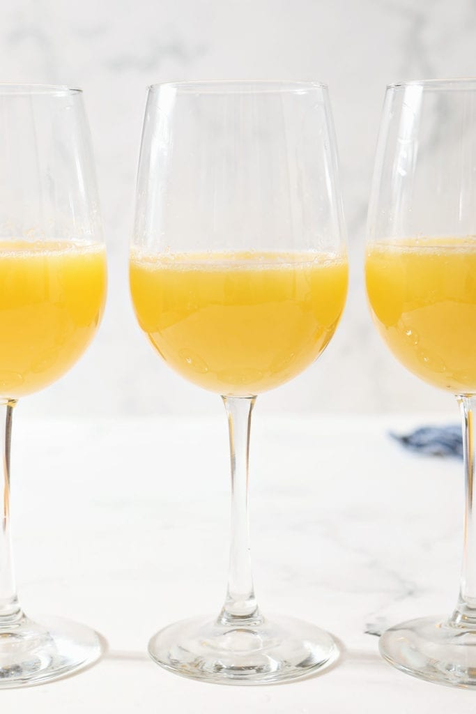 Three wine glasses holding orange drinks sit on a marble countertop
