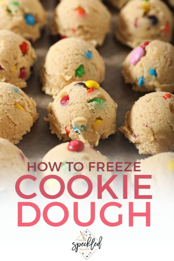 Dough balls full of M&Ms sit on a baking sheet before freezing with the text 'how to freeze cookie dough'