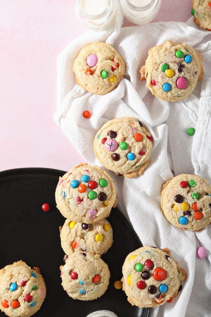 M&M Cookies sit on a black plate and a white towel