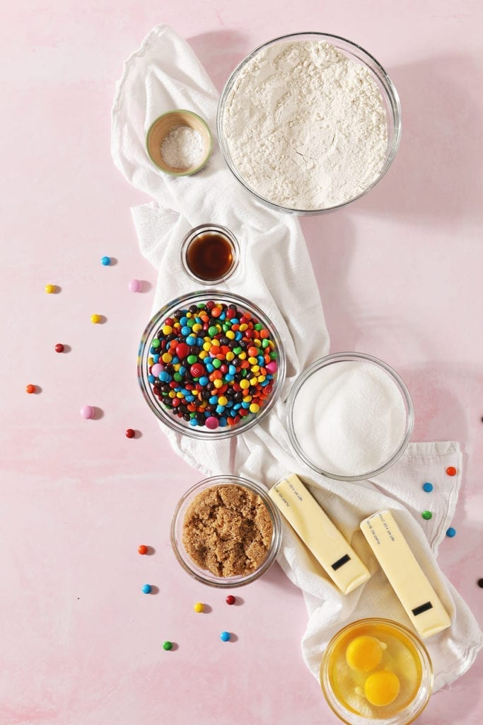 Ingredients to make M&M sugar cookies in bowls sit on a white towel on top of a pink countertop
