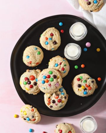 M&M Cookies sit on a black plate next to glasses of milk on a pink countertop