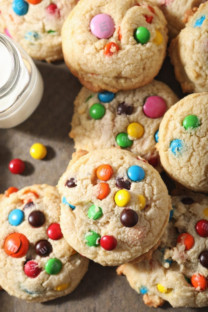 Close up of stacked M&M cookies next to a glass of milk