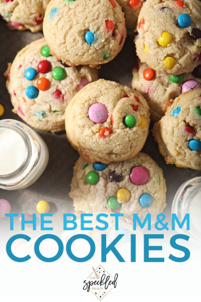 Close up of stacked M&M cookies next to a glass of milk with the text 'the best m&m cookies'