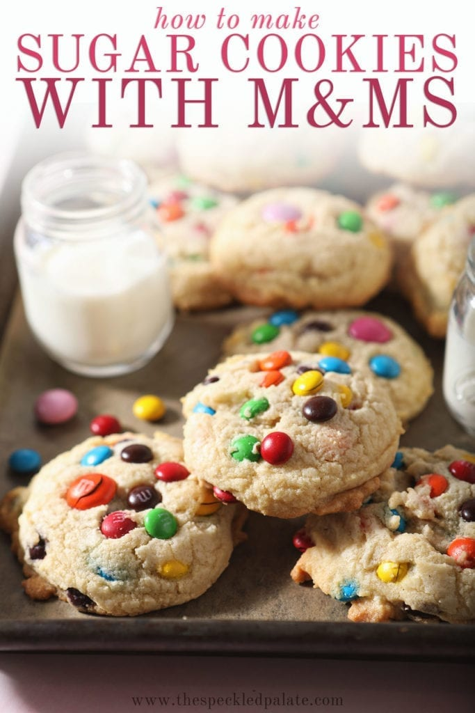 A baking sheet holds several M&M cookies next to a glass of milk with the text 'how to make sugar cookies with m&ms'