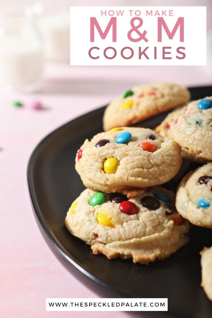 A black plate holds stacked cookies on a pink surface with the text 'how to make m&m cookies'