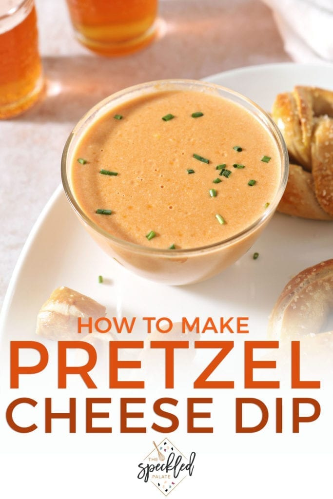 Close up of a bowl of cheese sauce on a white platter next to pretzels with the text 'how to make pretzel cheese dip'