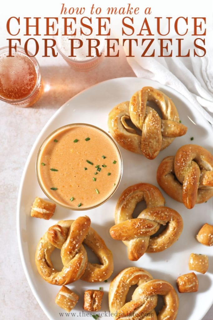 Soft baked pretzels sit around a bowl of cheese dip on a white platter with the text 'how to make a cheese sauce for pretzels'
