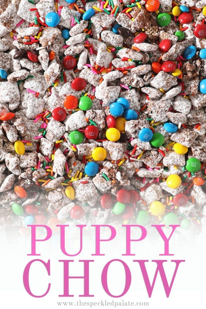Close up of chocolate candies and sprinkles on top of a sweet snack mix with the text 'puppy chow'