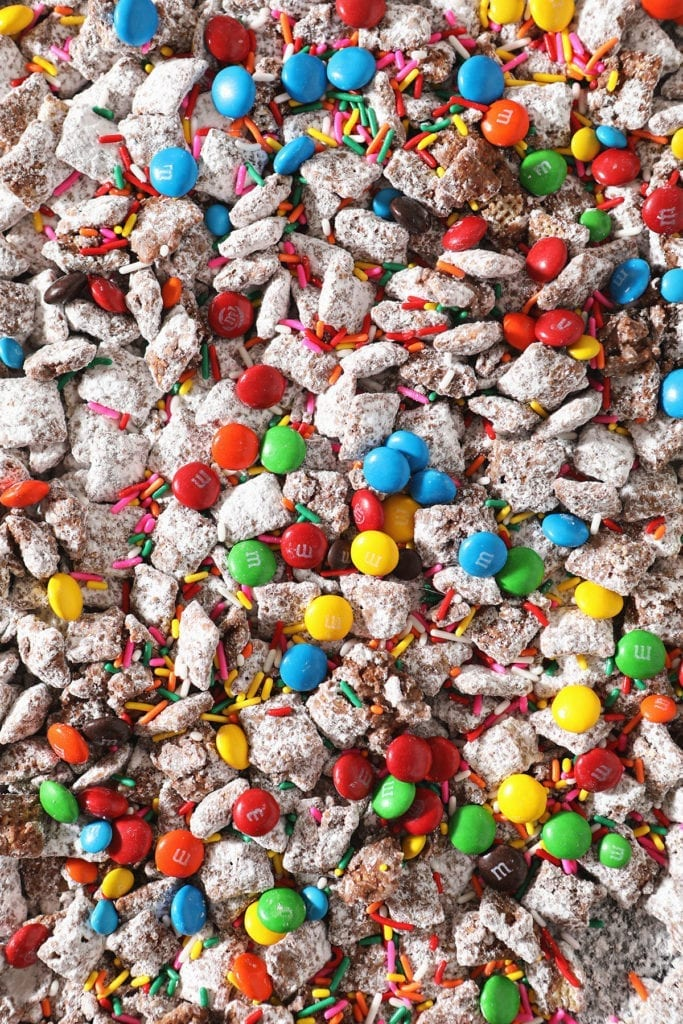 Close up of chocolate candies and sprinkles on top of a sweet snack mix