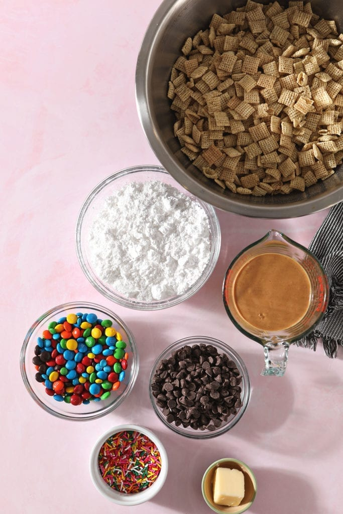 Ingredients for Chex Mix Puppy Chow in bowls on a pink countertop