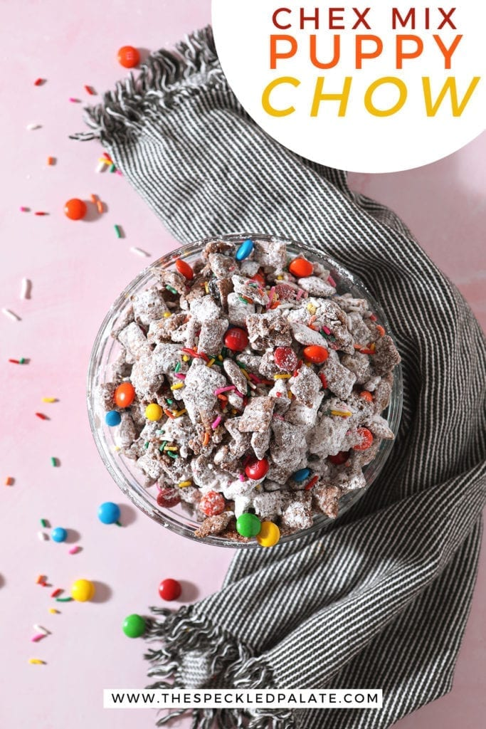 A bowl of rainbow puppy chow sits on a pink countertop next to a gray striped towel with the text 'chex mix puppy chow'