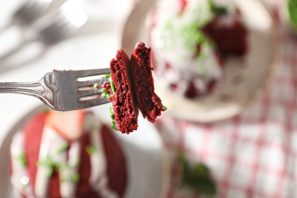 A fork spears pieces of red velvet pancakes and their garnishes above a table holding plates of the pancakes