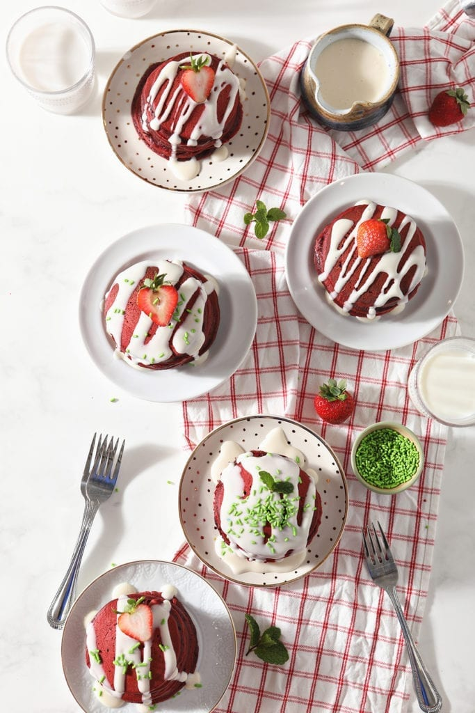 Five plates holding garnished red pancakes sit on a red and white towel on a marble countertop