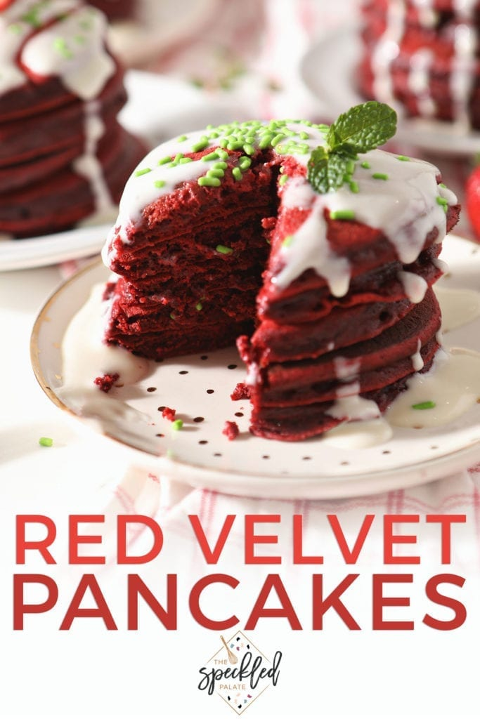 Close up of a stack of pancakes with glaze and green sprinkles with the text 'red velvet pancakes'