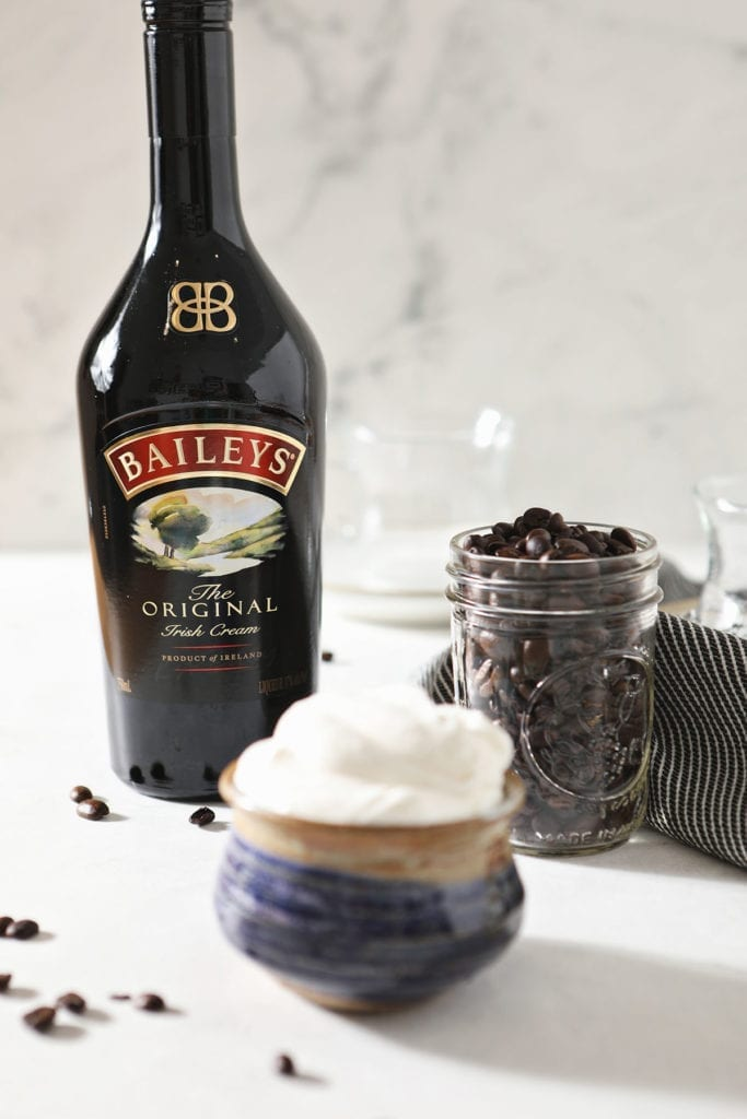 A bottle of Irish Cream, a jar of coffee beans and a bowl of whipped cream sit together on a marble countertop