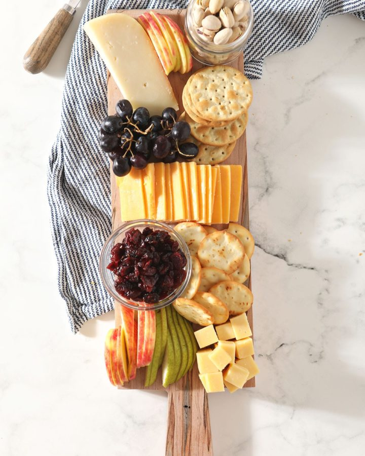 Fruit, cheese, crackers and other snacks on a wooden board