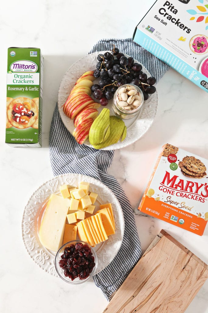 Cheeses, fruits and boxes of crackers on a blue striped towel