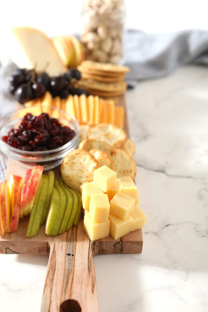 Stacked cheese cubes next to sliced fruit on a board