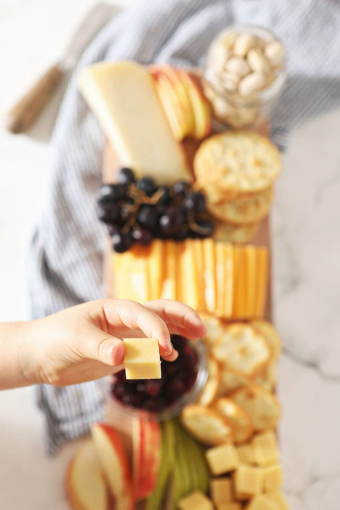 A child holds a cube of cheese above a snack board