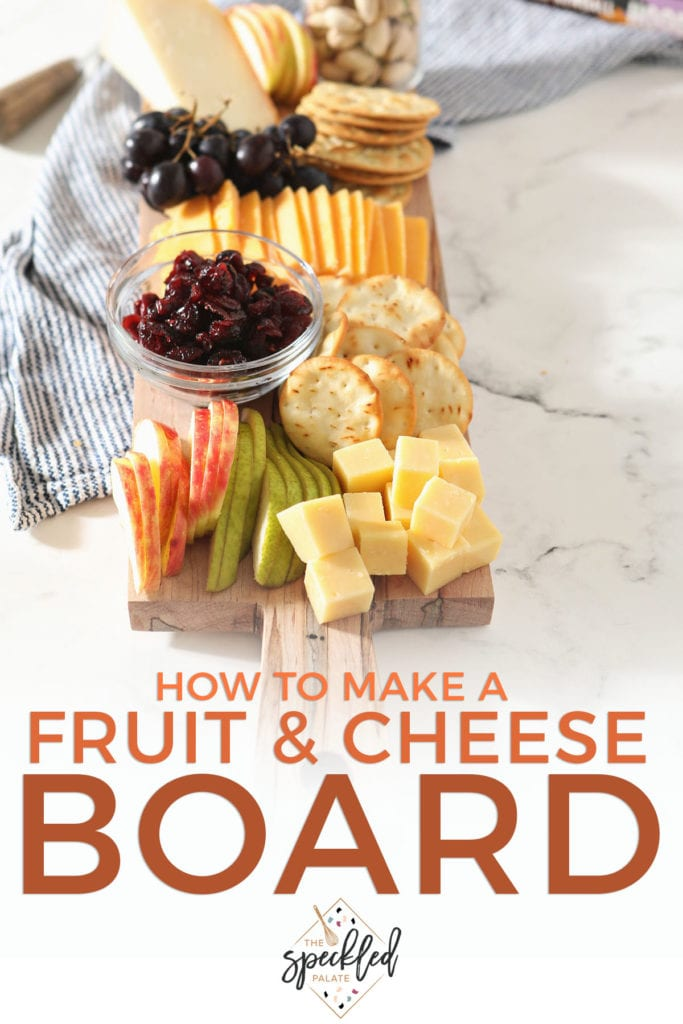 Stacked cheese cubes next to sliced fruit on a board with the text 'how to make a fruit & cheese board'