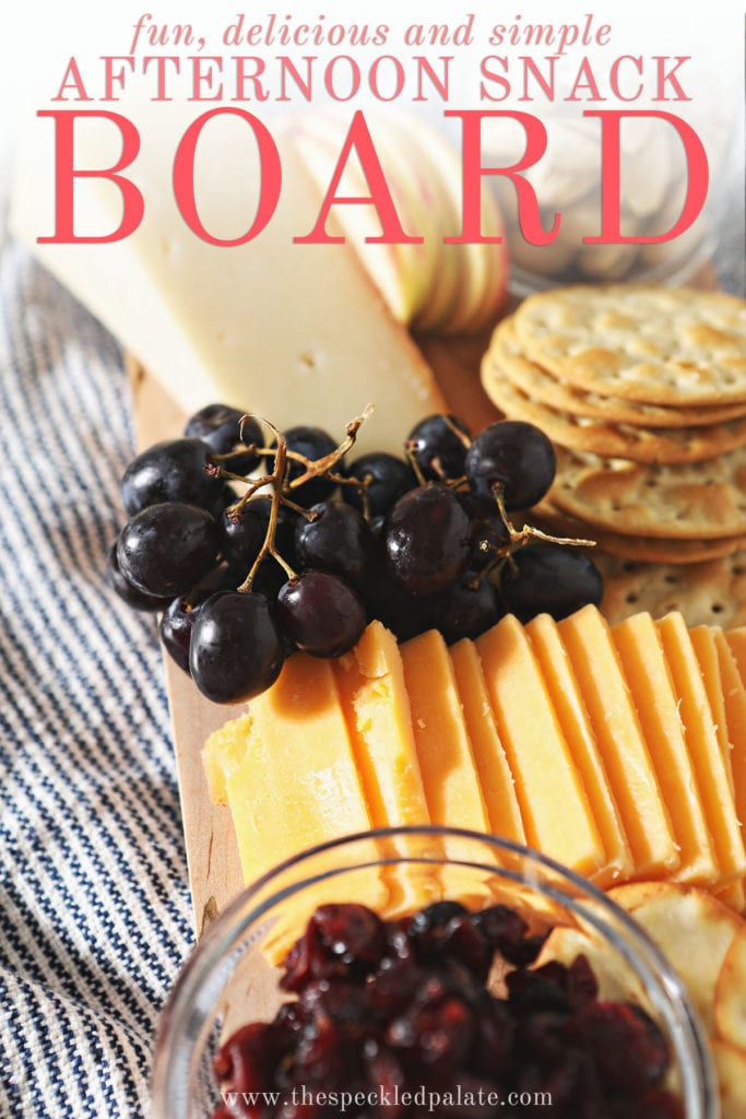 Grapes, cheese and crackers on a board with the text 'fun, delicious and simple afternoon snack board'
