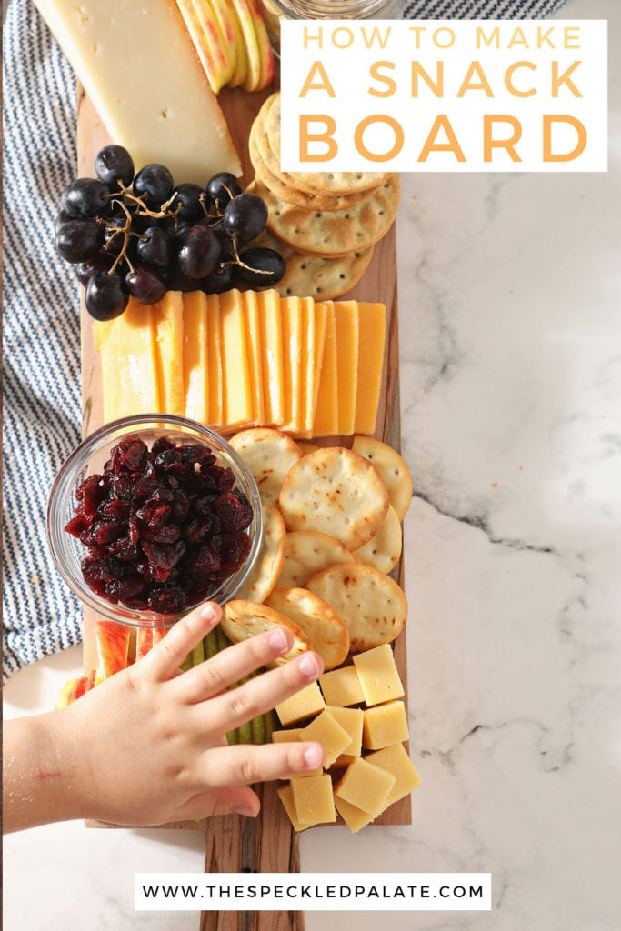 A child reaches for cubed cheese on a wooden board with the text 'how to make a snack board'
