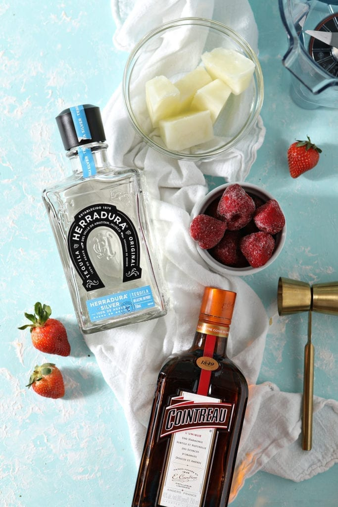 A bottle of tequila and a bottle of Cointreau sit on top of a white kitchen towel next to frozen strawberries and yellow ice cubes