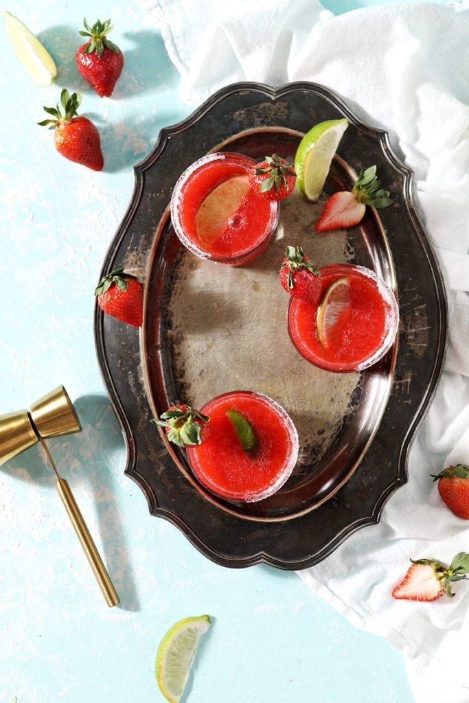 Three Frozen Strawberry Margaritas sit on a silver tray next to strawberries, lime wedges and a gold jigger