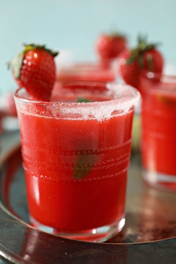Close up of a strawberry margarita rimmed with sugar and garnished with a strawberry and a lime wedge
