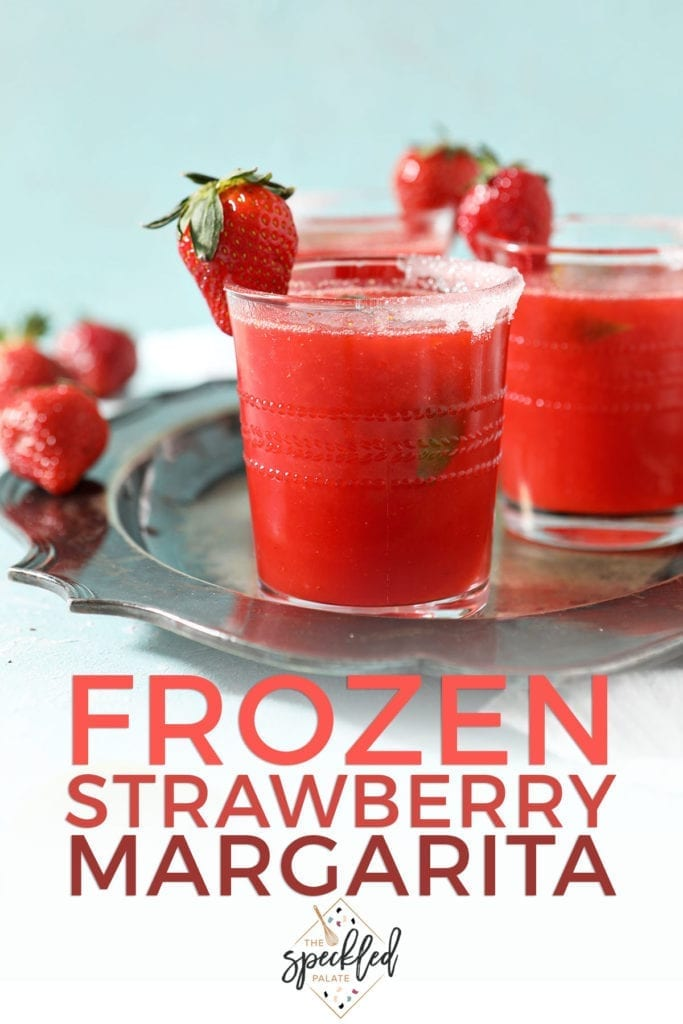 A silver tray holds three red drinks garnished with strawberries with the text 'frozen strawberry margarita'