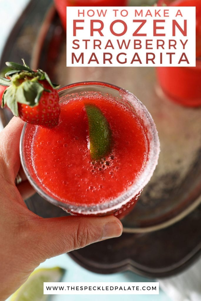 A woman holds a strawberry margarita garnished with a lime wedge and a strawberry with the text 'how to make a frozen strawberry margarita'