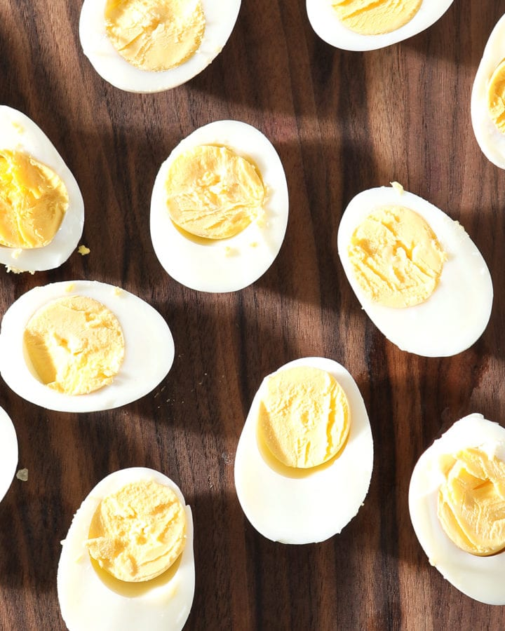 Several halved hard boiled eggs sit on a dark wooden cutting board