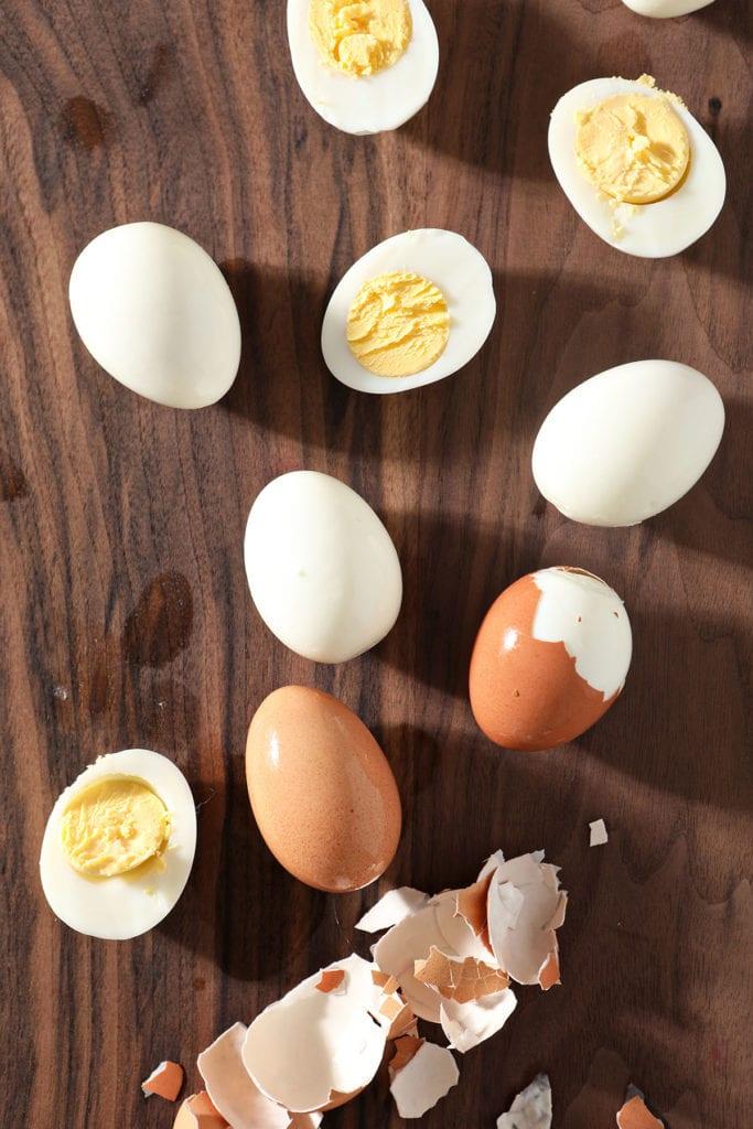 Hard boiled eggs are peeled on a dark wood cutting board