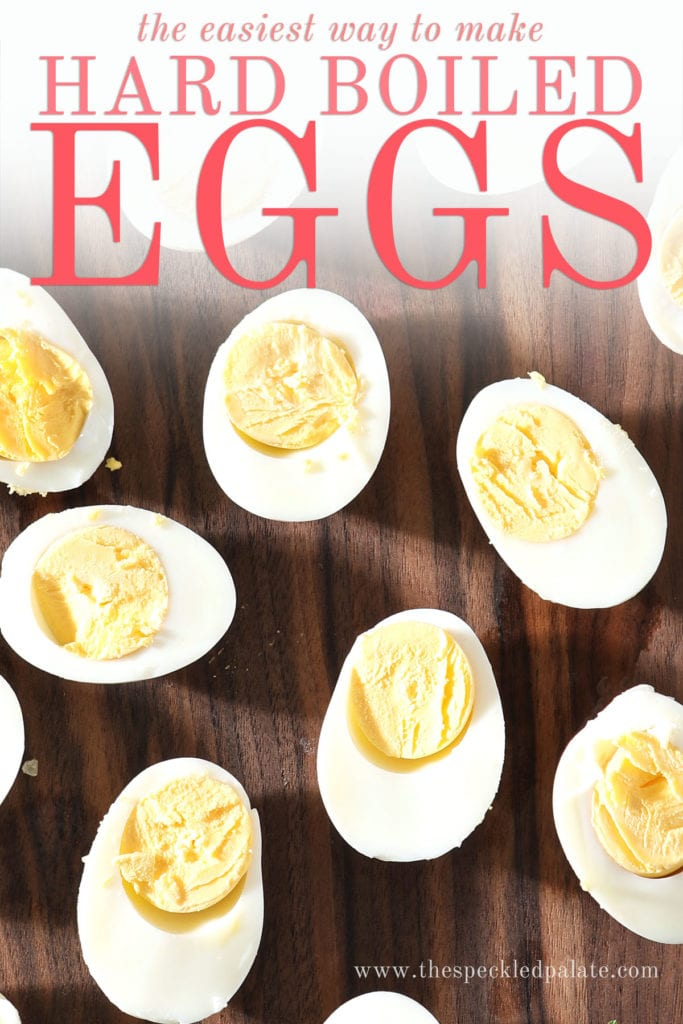 Several halved hard boiled eggs sit on a dark wooden cutting board with the text 'the easiest way to make hard boiled eggs'